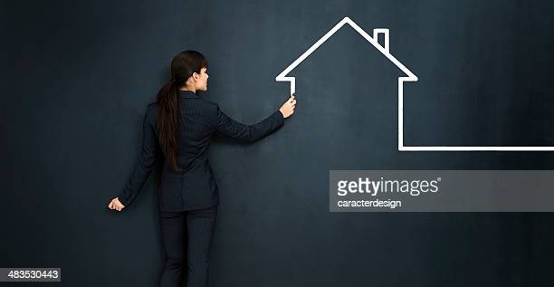 Woman drawing a house on big blackboard