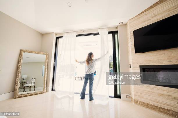 Woman drawing apart bedroom curtains