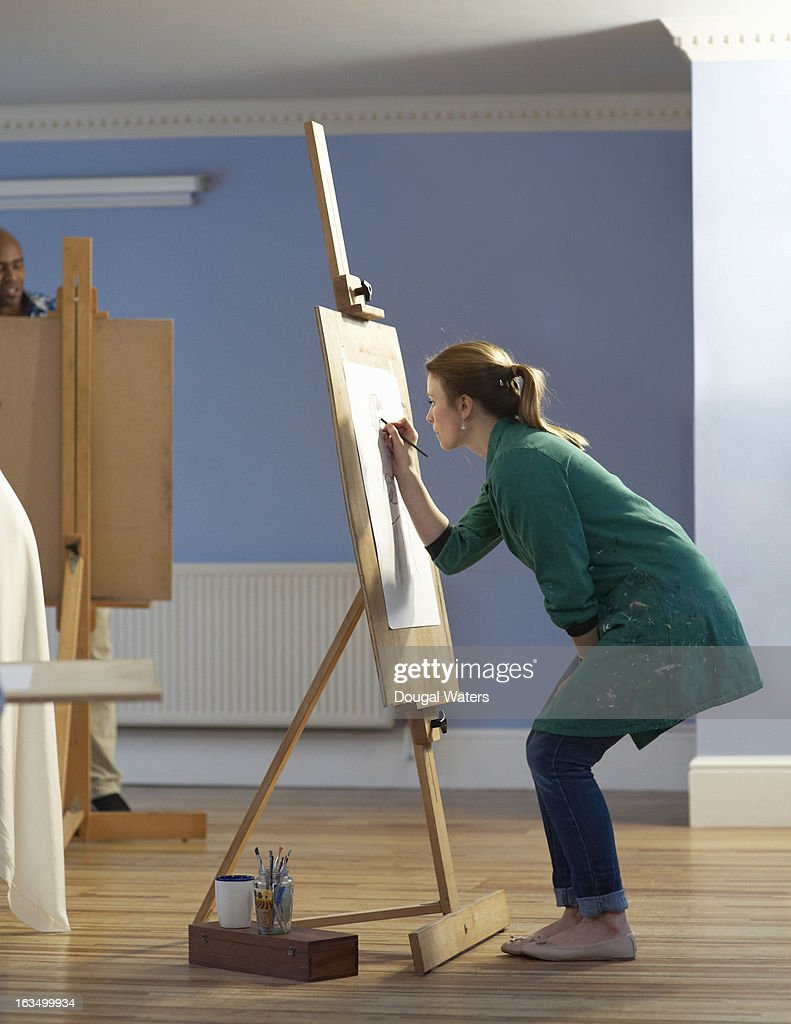 a woman drawing at an easel stock photo getty images