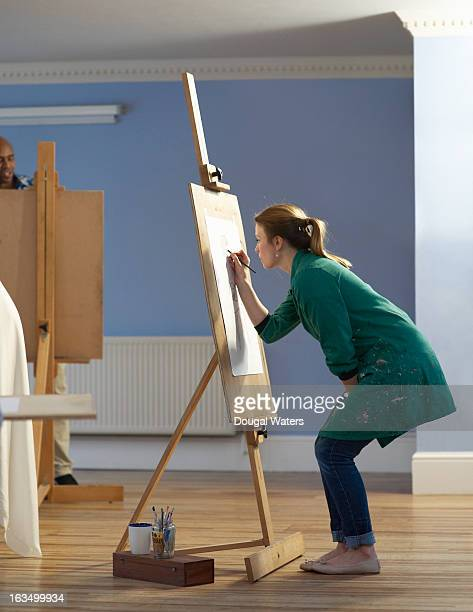 A woman drawing at an easel.