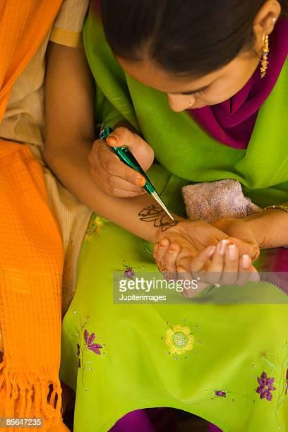 Woman drawing design using mendhi or henna