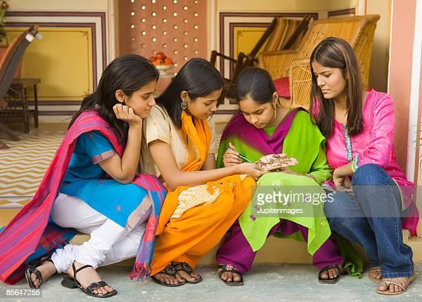 woman drawing design using mendhi or henna - salwar kameez stock photos and pictures