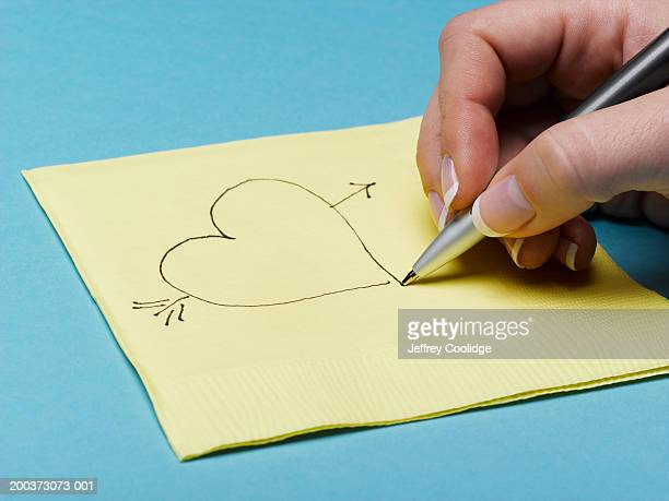 Woman drawing heart on napkin, close-up
