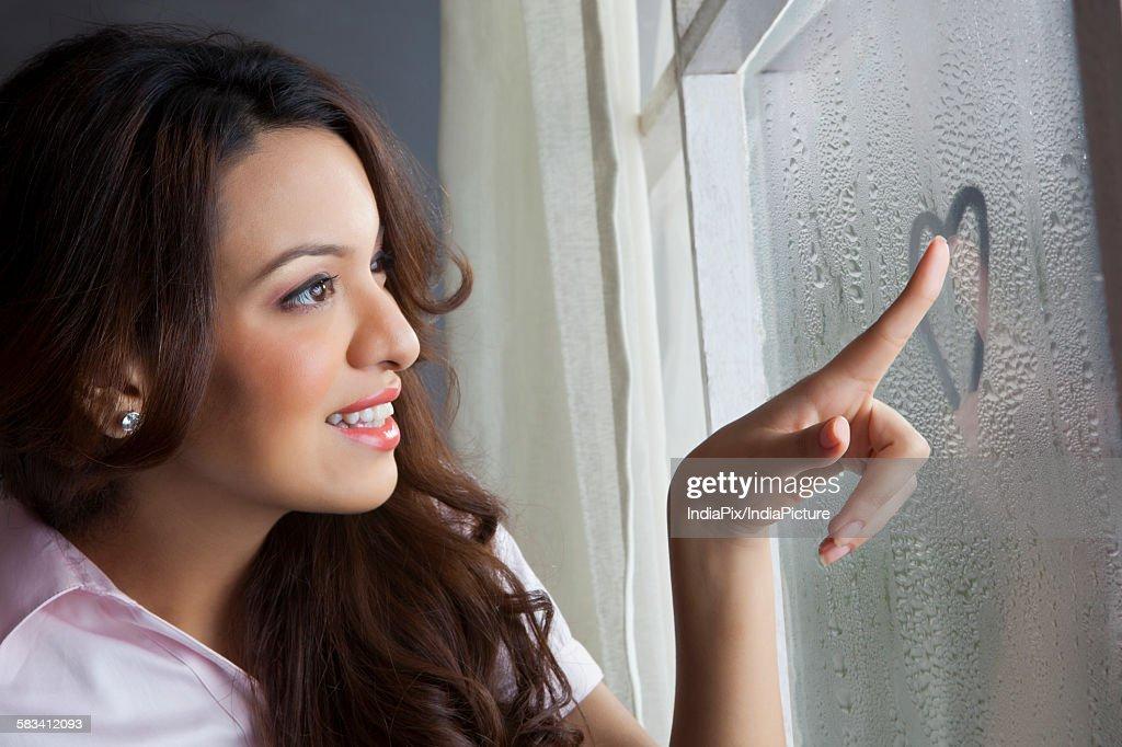 Woman drawing heart on window : Stock Photo