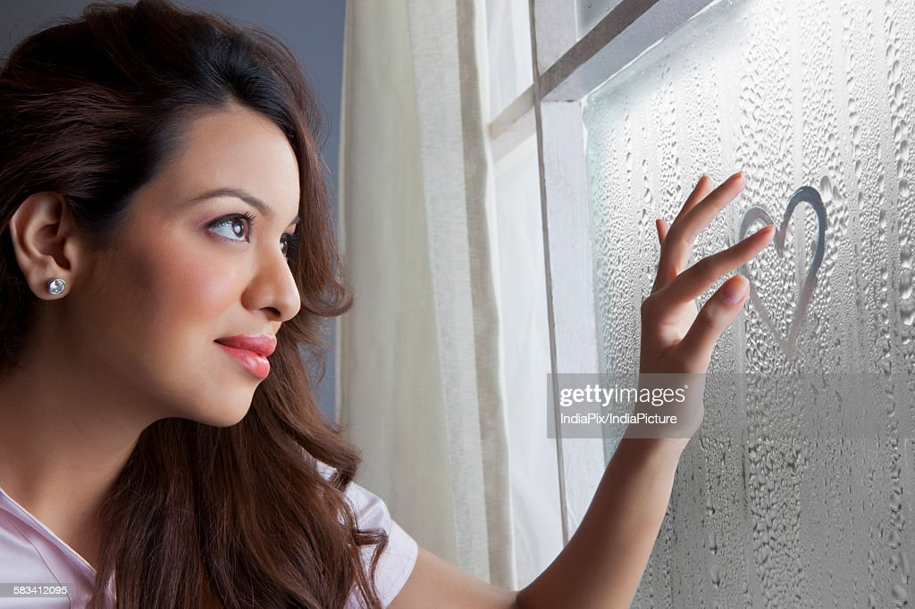 Woman drawing heart on window : Stock Photo