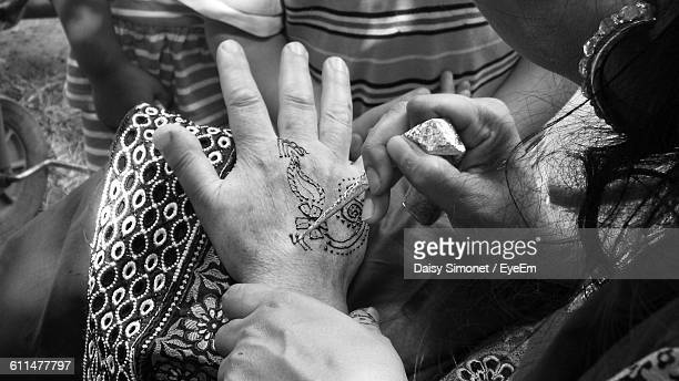 Woman Drawing Henna Tattoo On Hand