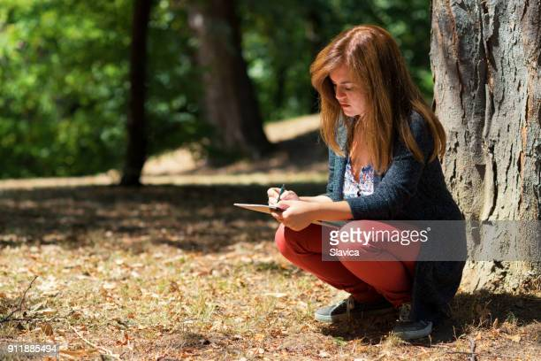woman drawing in the spring nature - illustrator stock photos and pictures