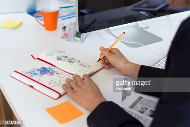 woman drawing into notebook at desk in office - skizze stock-fotos und bilder