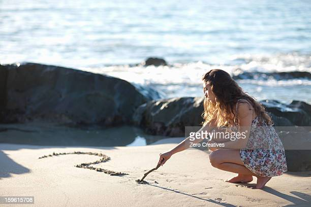 Woman drawing question mark in sand