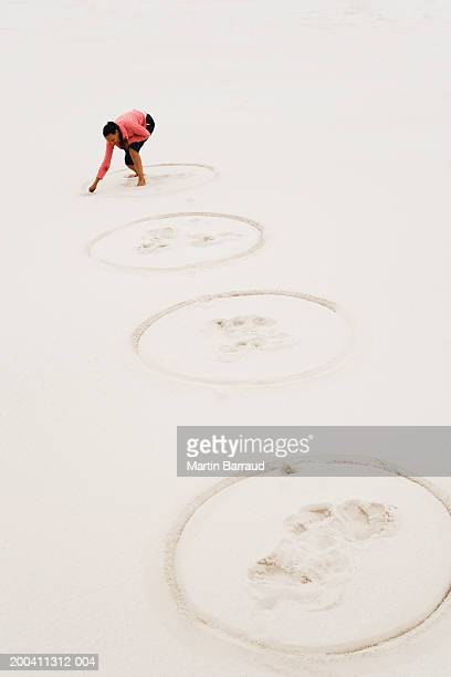 Woman drawing row of circles in sand on beach