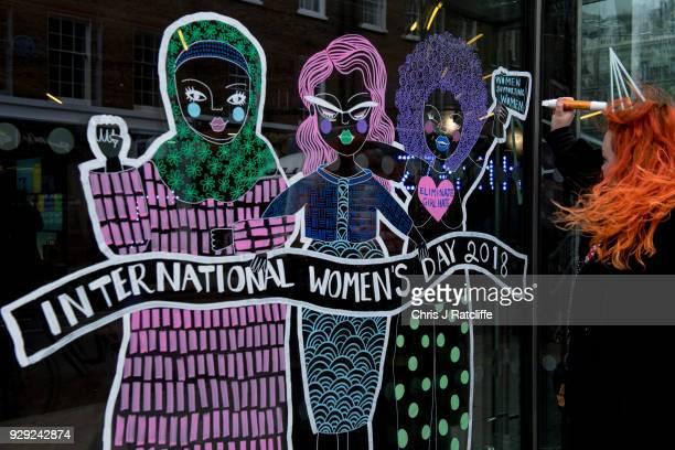 A woman draws a mural on a office window in Fitzrovia during International Women's Day on March 8 2018 in London United Kingdom International Women's...