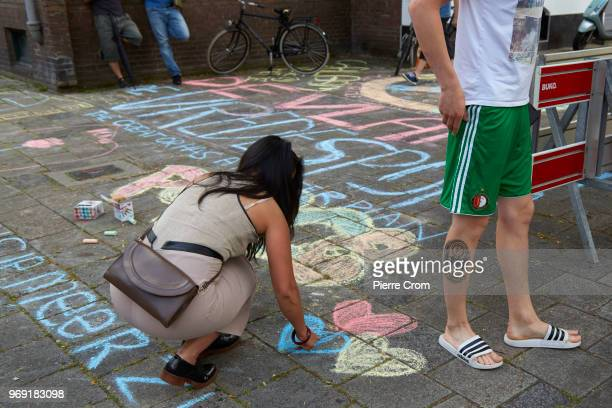 A woman draws hearts on the pavement next to a football fan outside the Laleli Mosque on June 7 2018 in Rotterdam NetherlandsThe antiIslam group...
