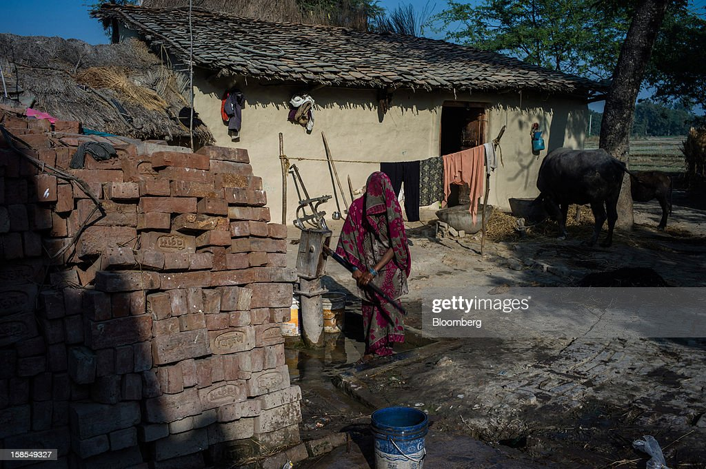 A woman draws water from a communal water pump in the village of Paltupur, Uttar Pradesh, India, on Friday, Dec. 7, 2012. India has the highest percentage of malnourished children in the world except for East Timor, according to the 2012 annual Global Hunger Index. Photographer: Sanjit Das/Bloomberg via Getty Images