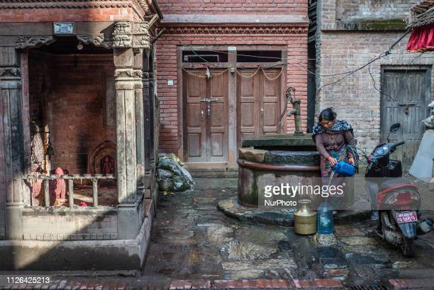 A woman draws water from a well in Bhaktapur Nepal in February 2019