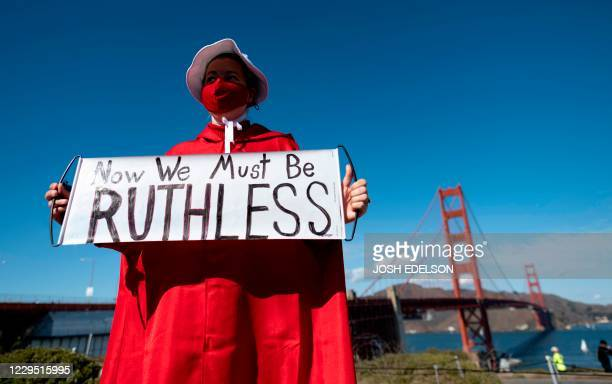 A woman dressed as a character from The Handmaid's Tale holds up a sign in homage to the late Supreme Court Justice Ruth Bader Ginsberg during a...