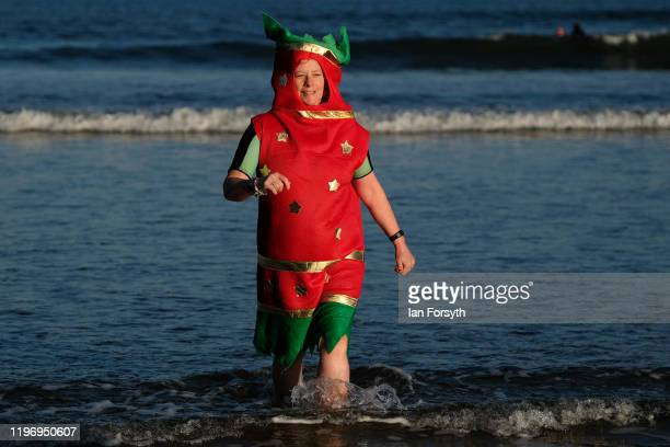 A woman dressed as a Christmas cracker walks from the sea after taking part in the New Year's Day Dip on January 01 2020 in Saltburn By The Sea...