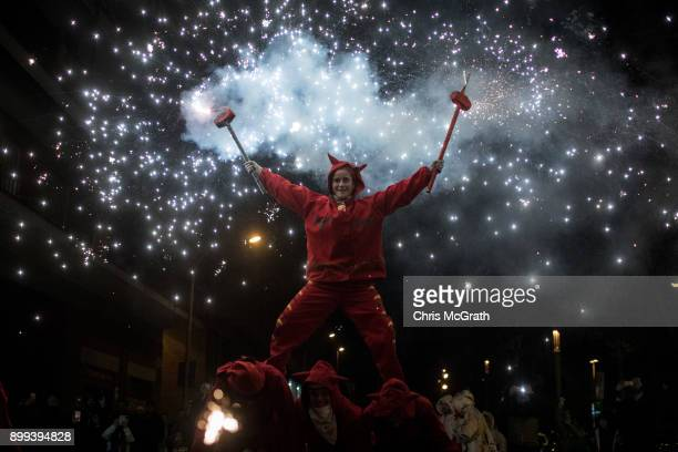 A woman dressed as a devil dances in the street under fire torches during the festival Nit de Llufes on December 28 2017 in Barcelona Spain People...