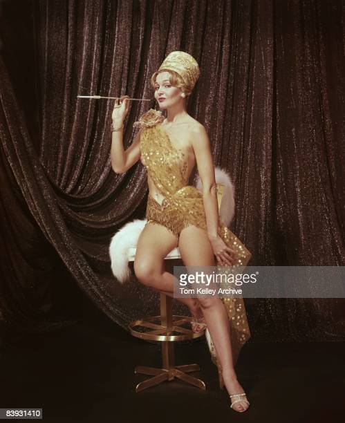 A woman dressed as a flapper flaunts the cigarette she's smoking in a cigarette holder ca1960s United States