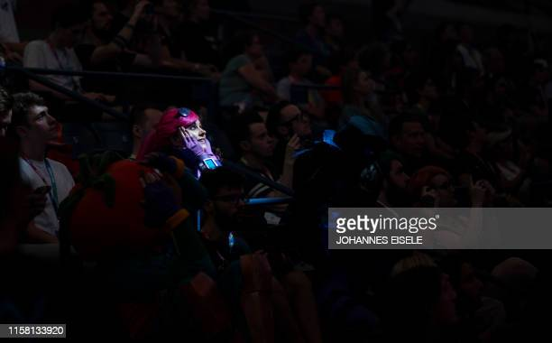 TOPSHOT A woman dressed as a Fortnite character reacts during the final seconds of the Duos competition at the 2019 Fortnite World Cup July 27 2019...