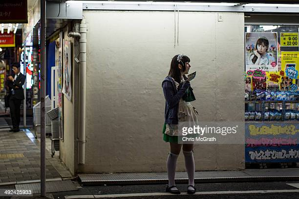 A woman dressed as a maid works on a street in Akihabara Electric Town on May 20 2014 in Tokyo Japan Akihabara gained the nickname Akihabara Electric...