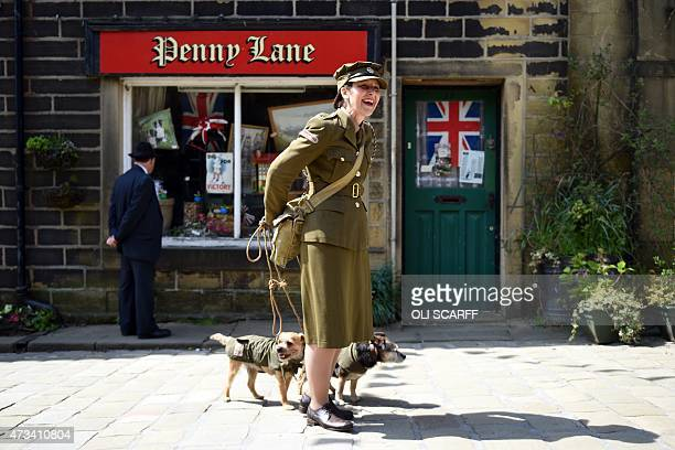 A woman dressed as a member of British Home Guard from World War II laughs as she attempts to unfurl her tangled dog leads on the first day of the...