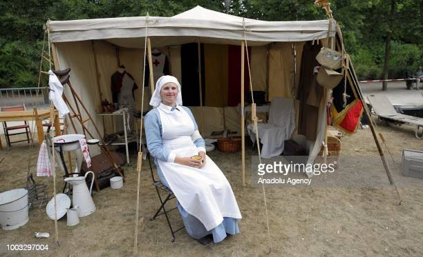 A woman dressed as a nurse sits in front of a hospital tent revival during military parade marking the 187th anniversary of Belgium's National Day in...