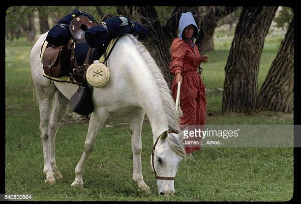 A woman dressed as a pioneer holds the tether of a horse eating grass on a trek from Fort Laramie to Fort Bridger with a group of people retracing...