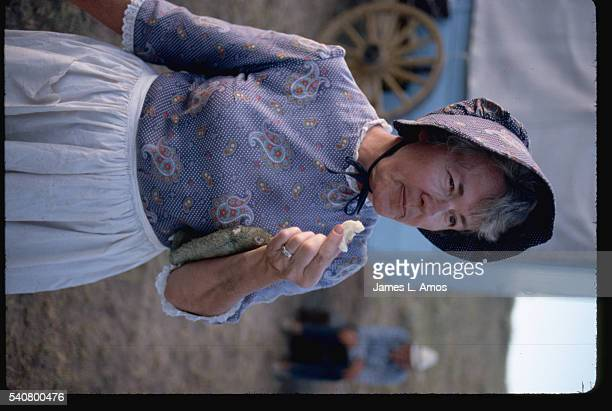 A woman dressed as a pioneer stands eating near a covered wagon while on a covered wagon vacation tour of the Oregon Trail designed to simulate the...