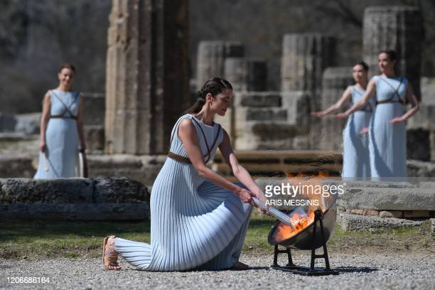 A woman dressed as a priestess lits the Olympic flame during the Olympic ceremony in ancient Olympia ahead of Tokyo 2020 Olympic Games on March 12...