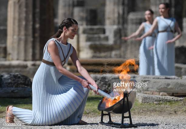 TOPSHOT A woman dressed as a priestess lits the Olympic flame during the Olympic ceremony in ancient Olympia ahead of Tokyo 2020 Olympic Games on...