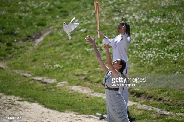 A woman dressed as a priestess releases a white dove next to torchbearer Greece's Anna Korakaki Rio 2016 gold medallist in the 25m pistol shooting...