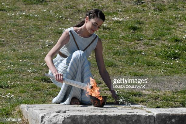 A woman dressed as a priestess takes part in the Olympic flame lighting ceremony in ancient Olympia ahead of Tokyo 2020 Olympic Games on March 12 2020