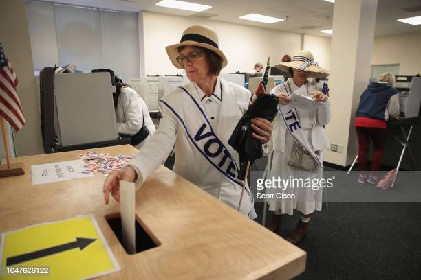 A woman dressed as a suffragette casts her ballot for the midterm elections at the Polk County Election Office on October 8 2018 in Des Moines...