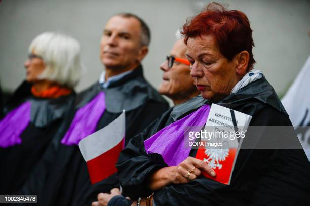 A woman dressed as a supreme court judge seen holding a polish constitution during the protest People demonstrate against reforms of the Supreme...