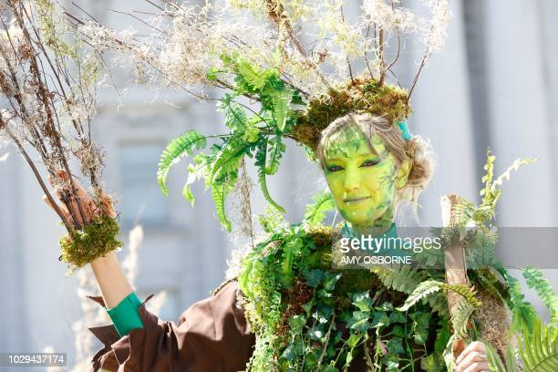 TOPSHOT A woman dressed as a tree with the group The Forgotten Solution poses for a picture at Civic Center Plaza after marching at the 'Rise For...