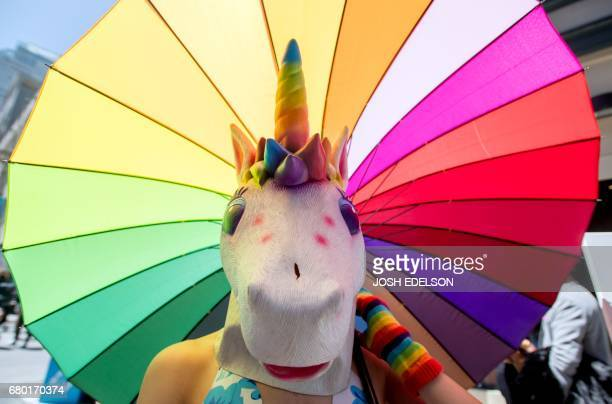 TOPSHOT A woman dressed as a unicorn holds a rainbow umbrella at the 18th annual How Weird Street Faire in San Francisco California on May 07 2017...