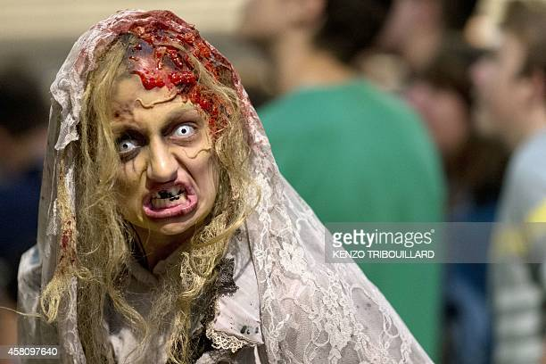 A woman dressed as a zombie entertains people waiting on October 30 2014 to see the show 'la Peste' at the Manoir de Paris haunted house in Paris AFP...