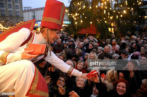 A woman dressed as an angel distributes slices of Stollen to visitors of the 574th socalled Striezelmarkt during the Christmas market's opening on...