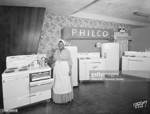 A woman dressed as Aunt Jemima is making pancakes on a pullout griddle at a stove which is part of a merchandise display at Evans Radio and TV Store...