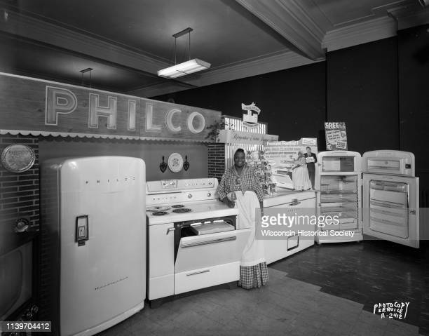 Woman dressed as Aunt Jemima standing with merchandise display at the Casey and O'Brien Store 124 West Mifflin Street featuring Philco appliances...