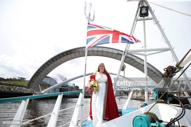 A woman dressed as Britannia poses on deck as a flotilla of fishing vessels passes under the Millennium Bridge in Newcastle northeast England on...