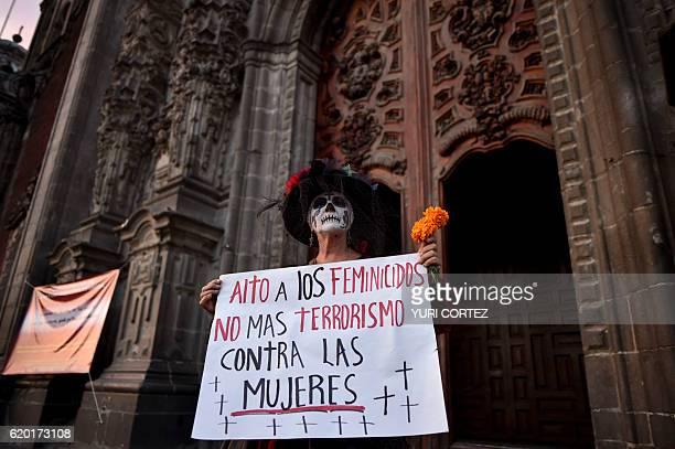 A woman dressed as Catrina holds a sign reading Stop femicides No more terrorism against women outside the Cathedral at the zocalo square in Mexico...
