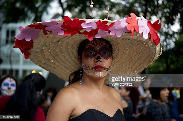 A woman dressed as Catrina poses for pictures at the Angel of Independence square before taking part in the Procession of the Catrinas along Reforma...