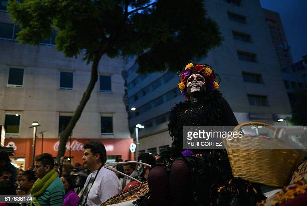 A woman dressed as Catrina takes part in the Catrinas Parade along Reforma Avenue in Mexico City on October 23 2016 Mexicans get ready to celebrate...