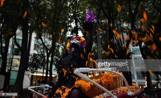 A woman dressed as Catrina throws pot marigold petals while taking part in the Catrinas Parade along Reforma Avenue in Mexico City on October 23 2016...