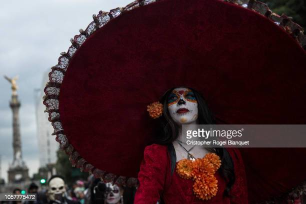A woman dressed as Catrina walks through Paseo de la Reforma the most important avenue in Mexico City on October 21 2018 in Mexico City Mexico This...
