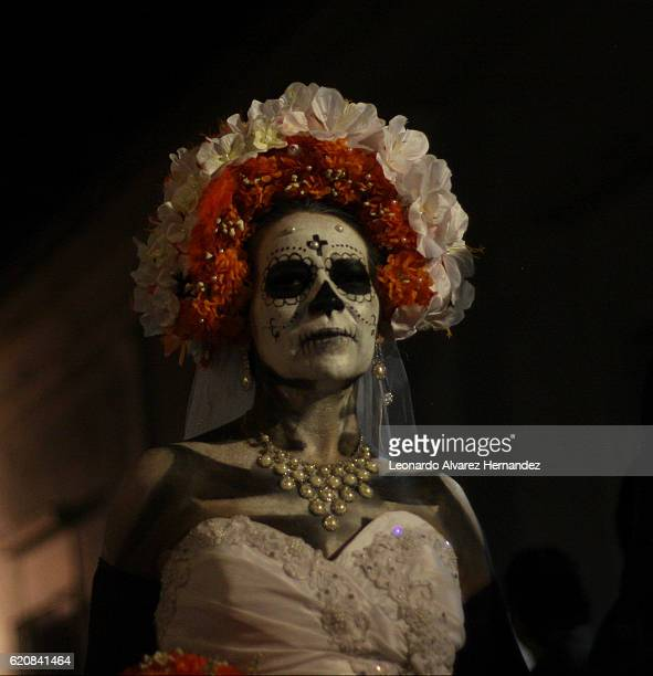 A woman dressed as Catrina with a wedding dress walks through the streets in Tlaquepaque as part of the Festival de la Muerte on November 2...