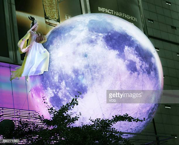 A woman dressed as Chang'e performs around a moon outside a shopping mall during the MidAutumn Festival on September 27 2015 in Jinhua Zhejiang...