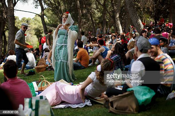 A woman dressed as 'Chulapa' tie her handkerchief during the San Isidro festivities at Pradera de San Isidro park on May 15 2014 in Madrid Spain...