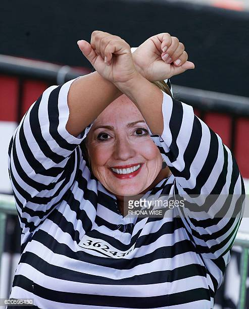 A woman dressed as Democratic presidential nominee Hillary Clinton in a prison outfit lifts her hands at a Trump rally in Miami Florida on November 2...